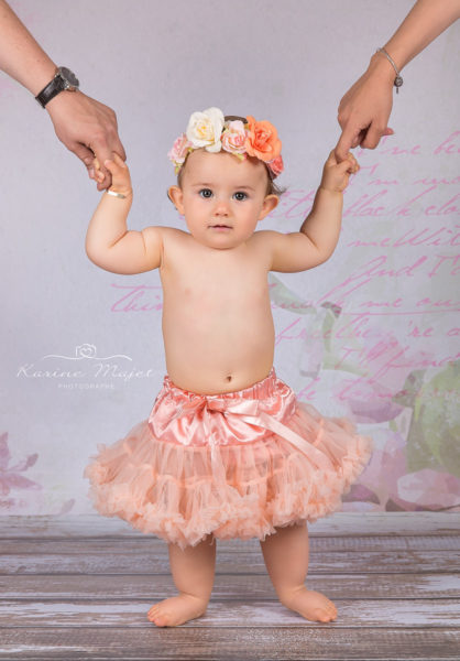 photo-anniversaire-bebe-tutu-rose-tient-mains-parents-karine-majet-photographe-418x600 (1)
