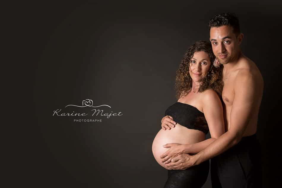 vive la grossesse couple sur fond noir photo de studio Karine Majet photographe