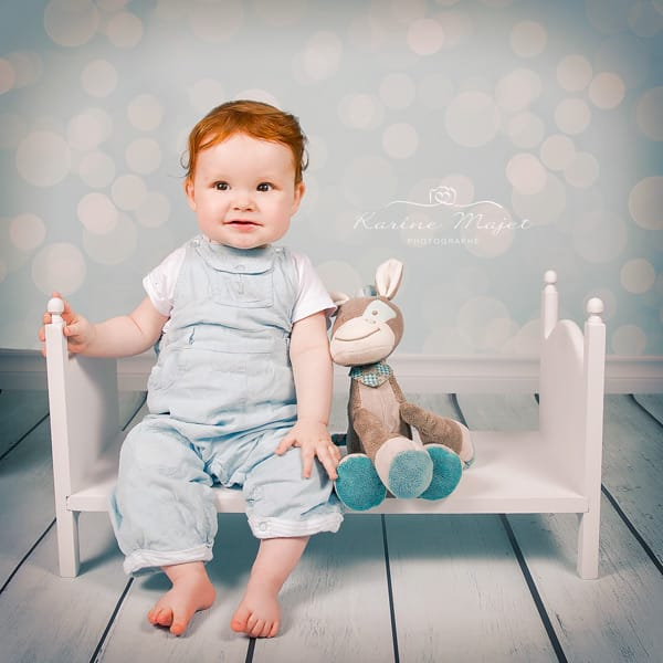 8 month baby photo shoot baby boy on a little white bed studio photo Paris